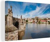 Beroemde Karelsbrug over de rivier de Moldau onder een prachtige wolkenhemel Canvas 180x120 cm - Foto print op Canvas schilderij (Wanddecoratie woonkamer / slaapkamer) XXL / Groot formaat!