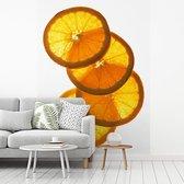 Fotobehang vinyl - Sinaasappel schijven op elkaar gestapeld met doorschijnend licht breedte 180 cm x hoogte 270 cm - Foto print op behang (in 7 formaten beschikbaar)