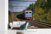 Fotobehang vinyl - Een trein op een spoorlijn breedte 450 cm x hoogte 300 cm - Foto print op behang (in 7 formaten beschikbaar)