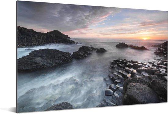 Zonsondergang en stromend water over de Giants Causeway in Noord-Ierland Aluminium 180x120 cm - Foto print op Aluminium (metaal wanddecoratie) XXL / Groot formaat!