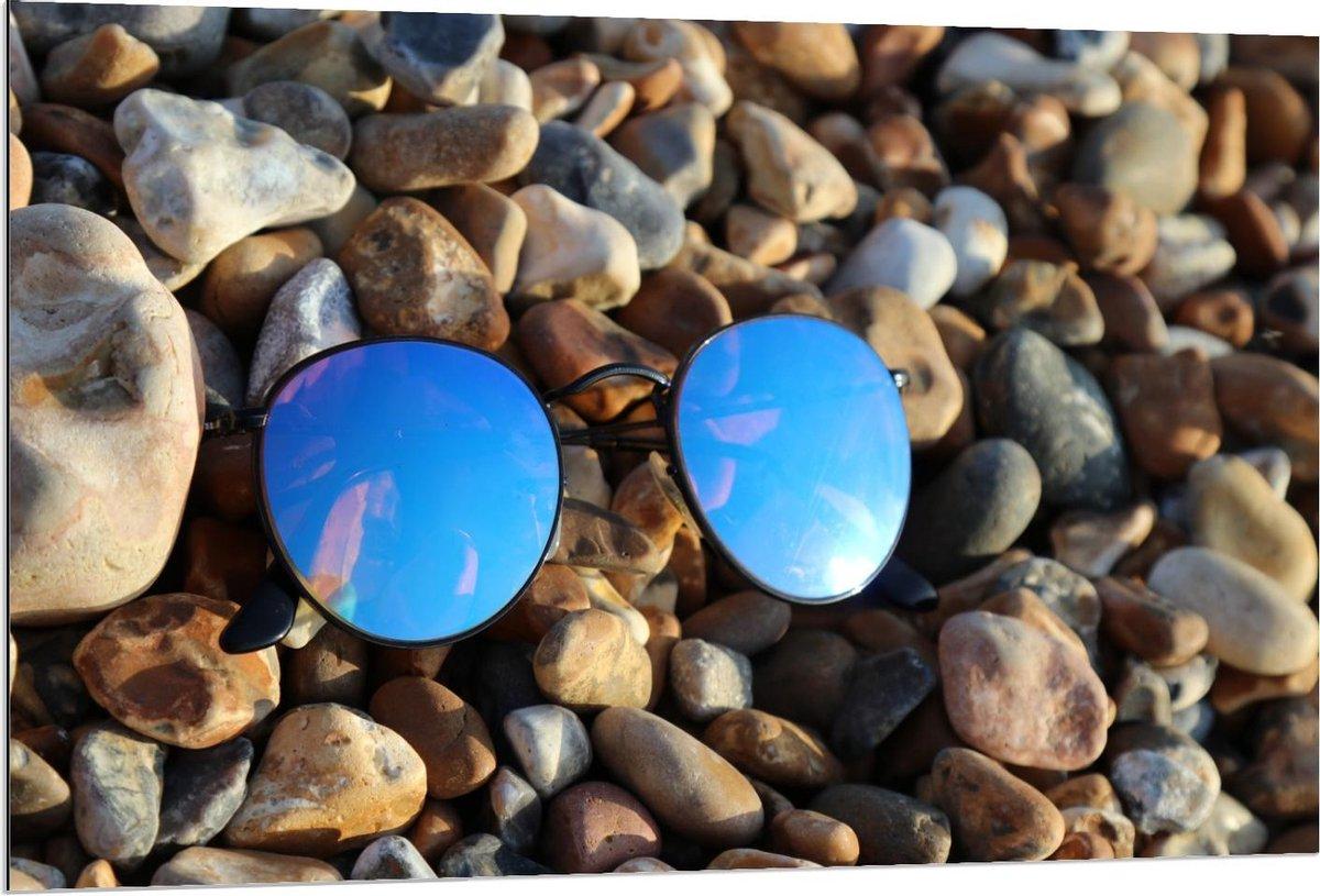 Dibond - Blauwe Zonnebril op Stenen - 120x80cm Foto op Aluminium (Wanddecoratie van metaal)