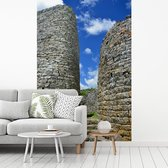 Fotobehang vinyl - De ingang van de ruïnes van het Afrikaanse Groot-Zimbabwe breedte 215 cm x hoogte 320 cm - Foto print op behang (in 7 formaten beschikbaar)
