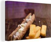 Een frikandel met kleine patat op een houten snijplank Canvas 30x20 cm - klein - Foto print op Canvas schilderij (Wanddecoratie woonkamer / slaapkamer)