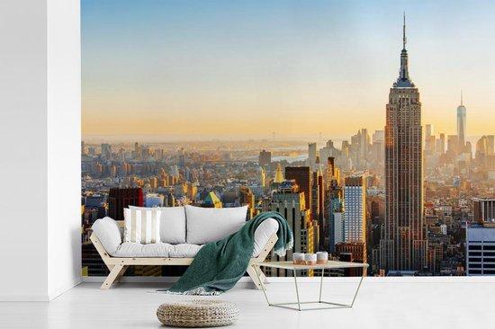 Fotobehang vinyl - Zonsondergang skyline van New York met het Empire State Building breedte 450 cm x hoogte 300 cm - Foto print op behang (in 7 formaten beschikbaar)