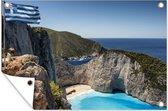 De Griekse vlag wappert boven Navagio Beach in Griekenland tuinposter 60x40 cm - klein - Tuindoek / Buitencanvas / Schilderijen voor buiten (tuin decoratie)