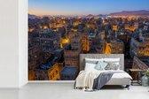 Fotobehang vinyl - Nachtelijke skyline verlichte straten van Sanaa in Jemen breedte 450 cm x hoogte 300 cm - Foto print op behang (in 7 formaten beschikbaar)