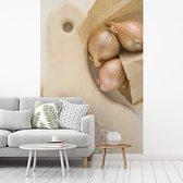 Gehakte en gepelde sjalotten op een houten snijplank fotobehang vinyl breedte 335 cm x hoogte 500 cm - Foto print op behang (in 7 formaten beschikbaar)