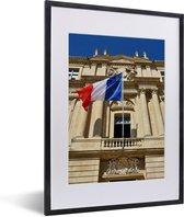 Foto in lijst - De vlag van Frankrijk wappert voor een gebouw fotolijst zwart met witte passe-partout klein 30x40 cm - Poster in lijst (Wanddecoratie woonkamer / slaapkamer)