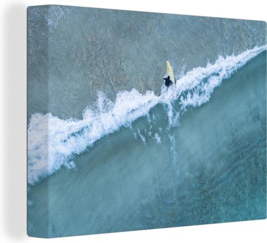 Luchtfoto van een surfer in de blauwe golven 160x120 cm - Foto print op Canvas schilderij (Wanddecoratie woonkamer / slaapkamer) XXL / Groot formaat!