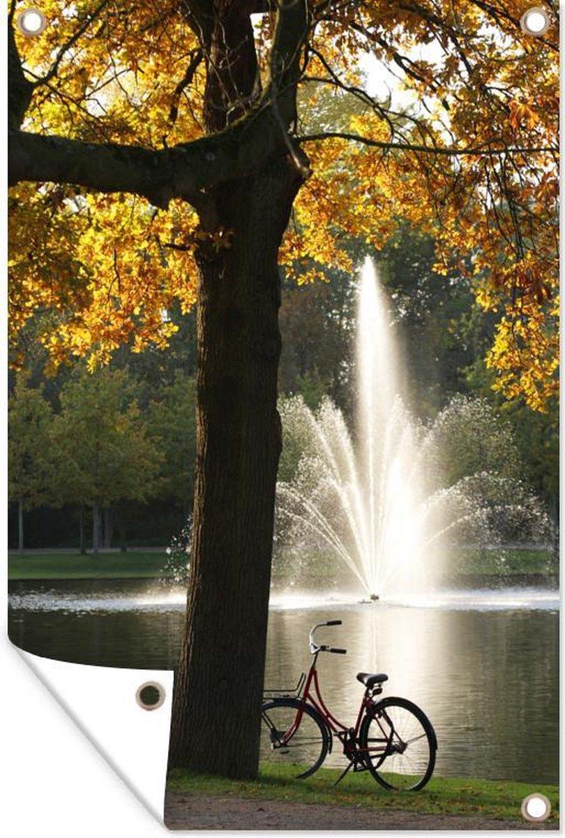 Tuinposter - Silhouet van een fiets voor een fontein in het Vondelpark in Amsterdam - 80x120 cm