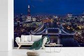 Fotobehang vinyl - De Tower Bridge verlicht in de nacht in Engeland breedte 450 cm x hoogte 300 cm - Foto print op behang (in 7 formaten beschikbaar)