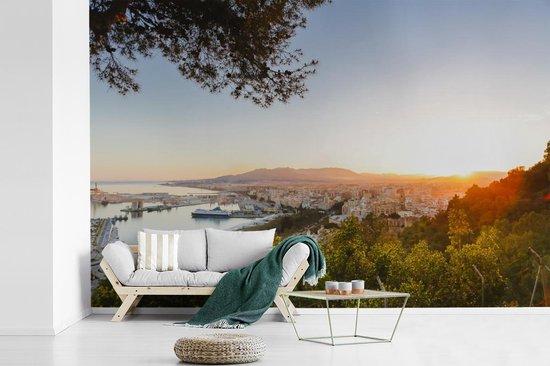 Fotobehang vinyl - Uitzicht op de haven van Málaga tussen de Spaanse bomen breedte 540 cm x hoogte 360 cm - Foto print op behang (in 7 formaten beschikbaar)