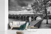Fotobehang vinyl - Zwart wit afbeelding van de brug in Maastricht breedte 330 cm x hoogte 220 cm - Foto print op behang (in 7 formaten beschikbaar)