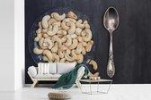 Glazen kom vol met cashewnoten op een zwarte tafel fotobehang vinyl breedte 540 cm x hoogte 360 cm - Foto print op behang (in 7 formaten beschikbaar)