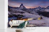 Fotobehang vinyl - Een verlichtte trein in de bergen breedte 450 cm x hoogte 300 cm - Foto print op behang (in 7 formaten beschikbaar)