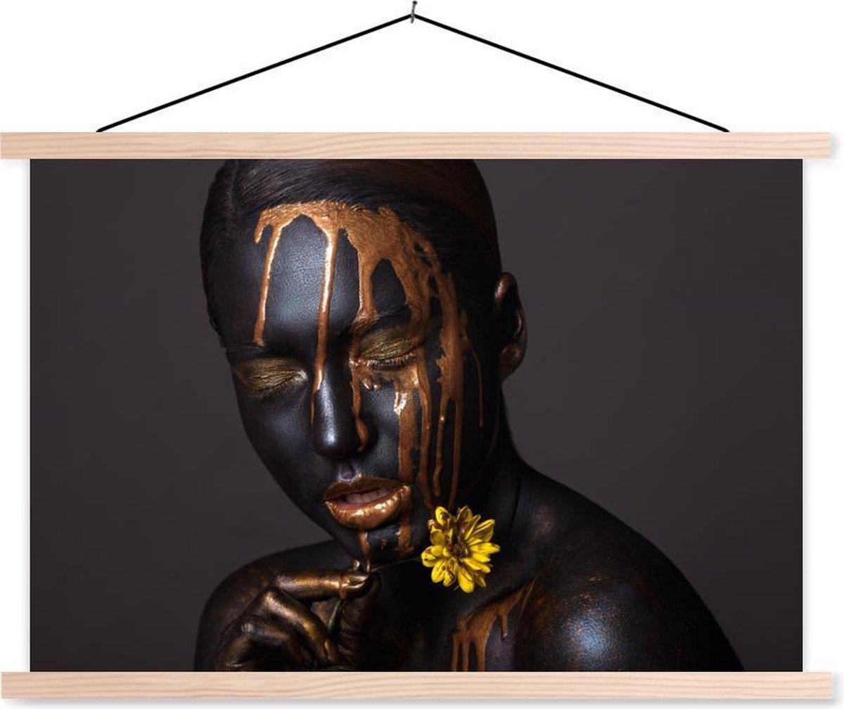 Een unieke afbeelding van een vrouw met make-up met gouden tinten. De vrouw draagt glanzende lippenstift. Het portret is gemakkelijk te combineren door de kleuren zwart en goud.