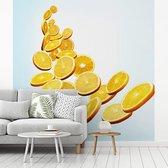 Fotobehang vinyl - Sinaasappel schijven vallen in lichtblauwe kleuren breedte 400 cm x hoogte 400 cm - Foto print op behang (in 7 formaten beschikbaar)