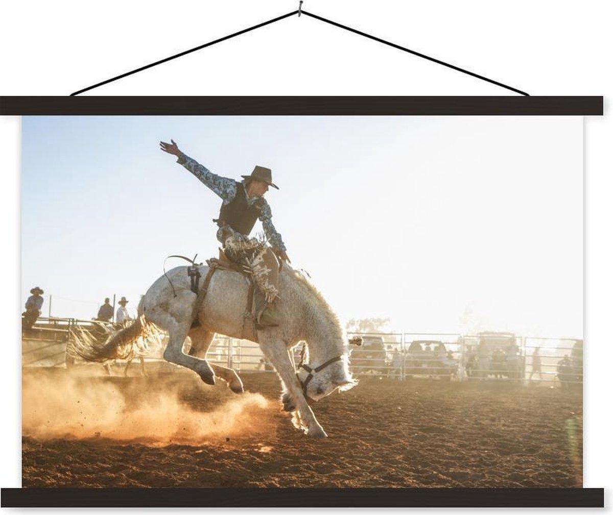 Cowboy op een paard tijdens de rodeo textielposter latten zwart 120x80 cm - Foto print op schoolplaat (wanddecoratie woonkamer/slaapkamer)