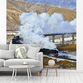 Fotobehang vinyl - Een stoomlocomotief over een karakteristieke brug breedte 260 cm x hoogte 260 cm - Foto print op behang (in 7 formaten beschikbaar)