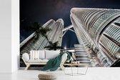 Fotobehang vinyl - De Petronas Towers vanaf onderen in de avond breedte 540 cm x hoogte 360 cm - Foto print op behang (in 7 formaten beschikbaar)