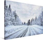Een besneeuwde weg wat omringt is door een winterlandschap Canvas 120x80 cm - Foto print op Canvas schilderij (Wanddecoratie woonkamer / slaapkamer)