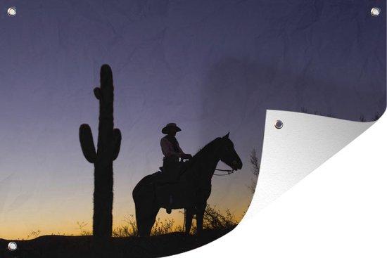 Tuinposter Cowboys - Silhouet van een cowboy bij een cactus met zonsondergang 90x60 cm - Tuindoek/Buitencanvas/Schilderijen voor buiten (tuin decoratie)