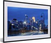 Foto in lijst - Het verlichte centrum van Minneapolis in de Verenigde Staten in de nacht fotolijst zwart met witte passe-partout 60x40 cm - Poster in lijst (Wanddecoratie woonkamer / slaapkamer)