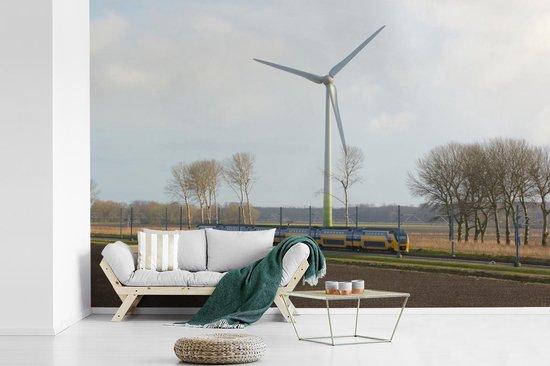 Fotobehang vinyl - Een trein midden in de weilanden breedte 450 cm x hoogte 300 cm - Foto print op behang (in 7 formaten beschikbaar)