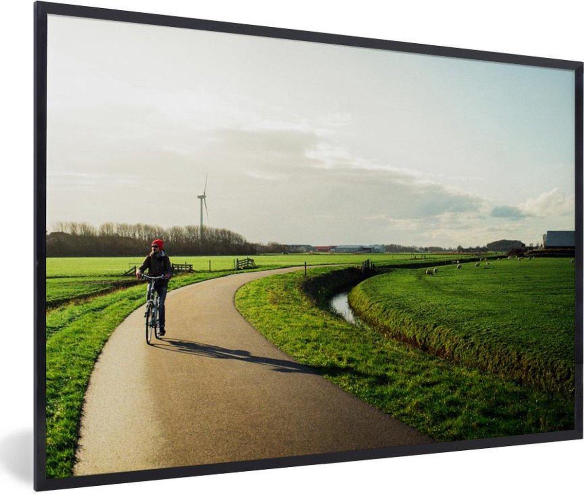 Poster met lijst Nederland - Man fietst langs weilanden - fotolijst zwart - 90x60 cm - Poster met lijst