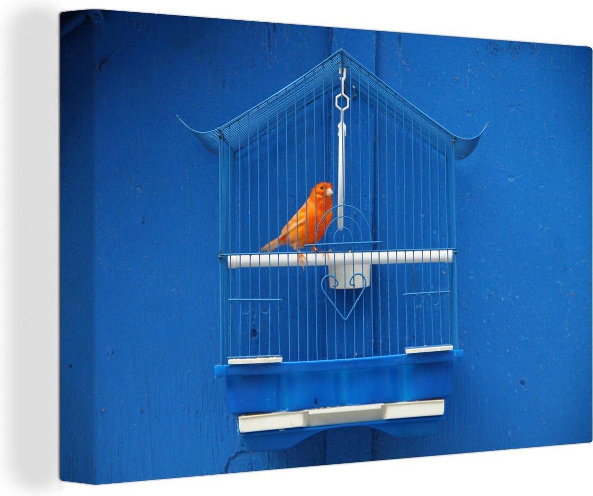 Canvas Schilderij Kanarie - Kanarie in een kooi tegen een blauwe muur canvas 2cm - 90x60 cm - Foto print op Canvas schilderij (wanddecoratie woonkamer / slaapkamer)