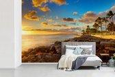 Fotobehang vinyl - Zonsondergang over rotsen en palmbomen op een strand in Hawaï breedte 600 cm x hoogte 400 cm - Foto print op behang (in 7 formaten beschikbaar)