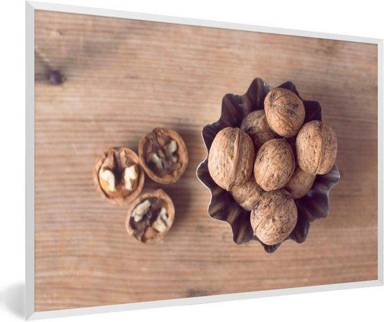 Foto in lijst - Bruine walnoten in een kom op een houten lijst fotolijst wit 60x40 cm - Poster in lijst (Wanddecoratie woonkamer / slaapkamer)