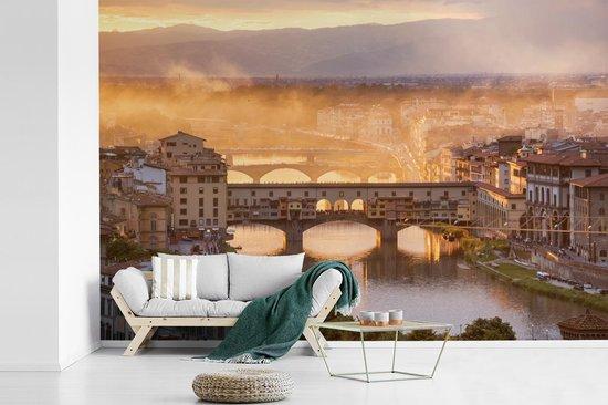 Fotobehang vinyl - Mist dampen boven de Ponte Vecchio in Florence breedte 330 cm x hoogte 220 cm - Foto print op behang (in 7 formaten beschikbaar)