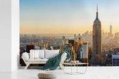 Fotobehang vinyl - Zonsondergang skyline van New York met het Empire State Building breedte 600 cm x hoogte 400 cm - Foto print op behang (in 7 formaten beschikbaar)