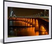 Foto in lijst - Verlichting van de Waalbrug in de Nederlandse stad Nijmegen fotolijst zwart met witte passe-partout 60x40 cm - Poster in lijst (Wanddecoratie woonkamer / slaapkamer)