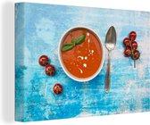 Kom tomatensoep op blauwe oppervlakte Canvas 140x90 cm - Foto print op Canvas schilderij (Wanddecoratie woonkamer / slaapkamer)