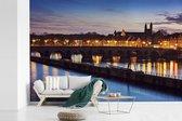 Fotobehang vinyl - Verlichte brug over de Maas in Maastricht breedte 450 cm x hoogte 300 cm - Foto print op behang (in 7 formaten beschikbaar)