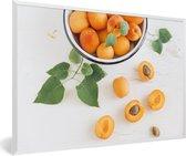 Foto in lijst - Oranje abrikozen in een kom op witte ondergrond fotolijst wit 60x40 cm - Poster in lijst (Wanddecoratie woonkamer / slaapkamer)