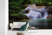 Fotobehang vinyl - Hoge waterval boven een rustig meertje in nationaal park Erawan breedte 450 cm x hoogte 300 cm - Foto print op behang (in 7 formaten beschikbaar)