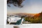 Uitzicht op de haven van Málaga tussen de Spaanse bomen fotobehang vinyl 330x220 cm - Foto print op behang