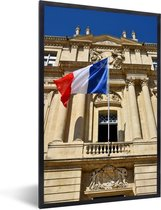 Foto in lijst - De vlag van Frankrijk wappert voor een gebouw fotolijst zwart 40x60 cm - Poster in lijst (Wanddecoratie woonkamer / slaapkamer)