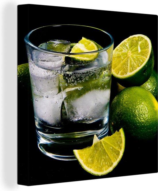Glas gin en tonic op ijs omgeven door limoenen Canvas 50x50 cm - Foto print op Canvas schilderij (Wanddecoratie woonkamer / slaapkamer)